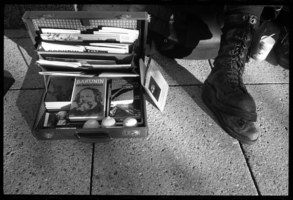 """A few weeks ago I was wandering around town with film in my camera and time on my hands. This is a portrait of Rusty (""""please keep my face out of the photo""""). I'd call Rusty and his friend Sonia travelers. I liked the way his big boots looked next to the briefcase packed with anarchist literature and three lemons."""