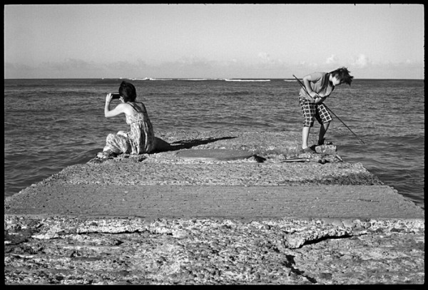 They seemed to be in two separate worlds. She, absorbed in photography. He, looking for fish to spear.