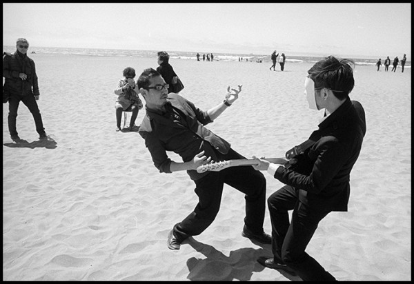Ocean Beach, San Francisco . A band was playing on sand. A complete set up, with a bandstand, generator, drums, guitars and really bad music. These two guys were carrying on slightly offstage. It seemed like a lesson in how to rock and roll.