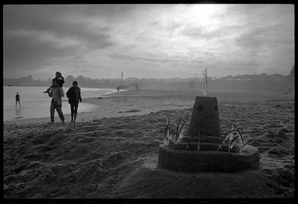 Sand castle and three people.
