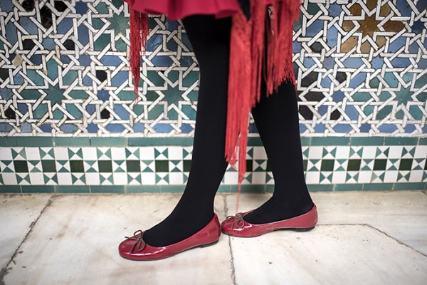 Fashion forward at the fort. Sevilla's Alcázar, an architectural wonder built in the 1300's, serves as a backdrop for red shoes.