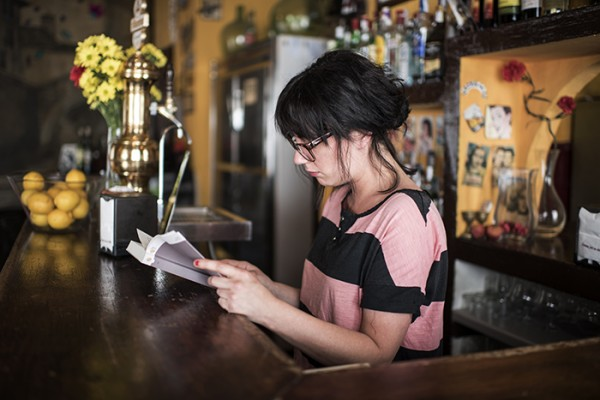 A bartender enjoys a quiet moment.