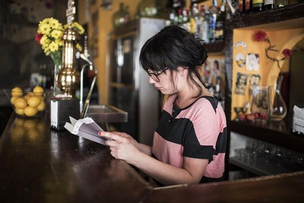 A bartender enjoys a quiet moment.