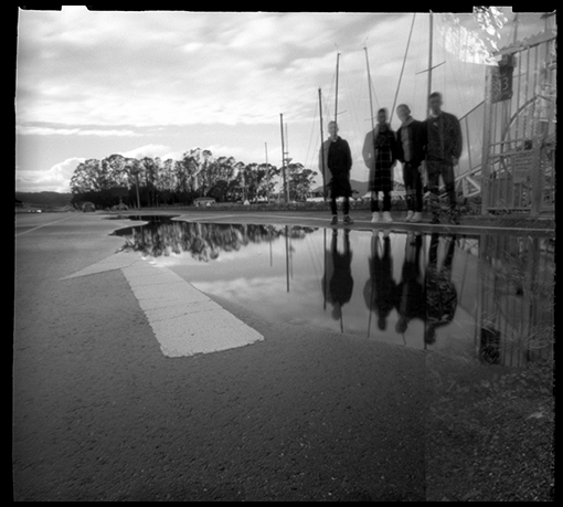Further experiments with the pinhole camera. I liked the scene. I was hanging around waiting for someone to pass by so I could have a figure in the photo. I asked these four guys to stand across the puddle and look in my direction. There's a little bit of overlap from the previous frame on the right side of the image. Still learning!